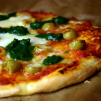 Selbst gemachte Pizza mit Mozzarella, Basilikumpesto und Oliven